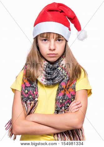 Half-length emotional portrait of caucasian girl wearing Santa Claus hat and scarf, sad. Schoolgirl in yellow t-shirt with arms folded. Holiday Christmas concept - unhappy cute child isolated on white background.
