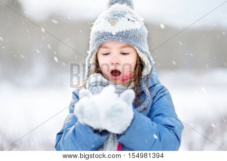 Funny Little Girl Catching Snowflakes In Winter Park