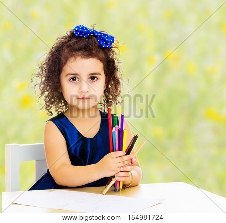 Cute little girl in blue dress, holds a lot of pencils . She paints at a table in a Montessori kindergarten.Bright, floral yellow-green blurred background.