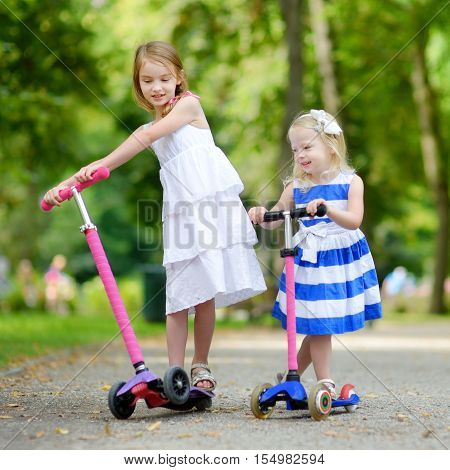 Two Little Sisters Riding Their Scooters