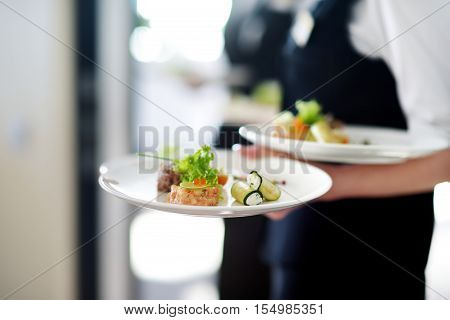 Waiter carrying plates with meat dish on some festive event party or wedding reception poster