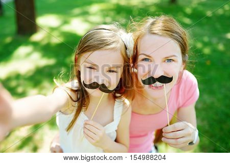 Mother And Daughter Playing With Paper Moustaches On A Stick