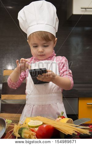 little cute girl playing in the kitchen and holding a smartphone