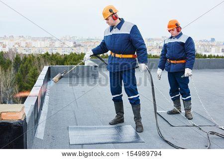 Flat roof installation. Heating and melting bitumen roofing felt