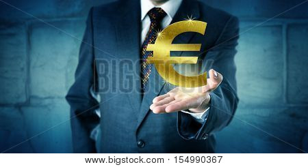 Currency trader showing a virtual golden Euro symbol hovering above the open palm of his raised left hand. Business concept and financial metaphor for interbank market forex wealth and investment.