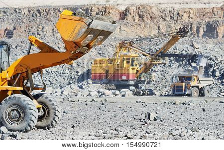 Heavy wheel loader extracting granite rock or iron ore at opencast mining quarry poster