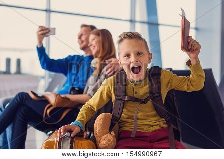 Yeeeaahh. Joyful smiling little boy holding passport and boarding pass at airport with his parents on background