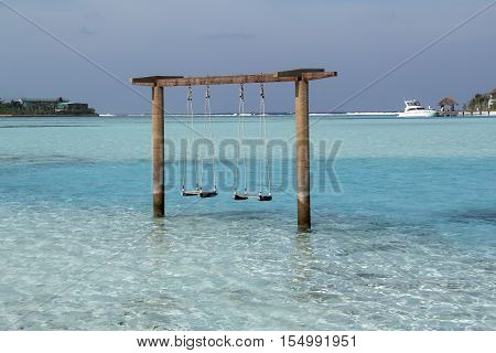 romantic swing straight into the turquise ocean water in Maldives beach