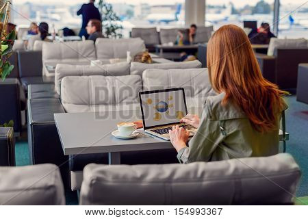 I love taking my work on go. Back view shot of young girl sitting on sofa in waiting hall of airport and working on laptop before boarding
