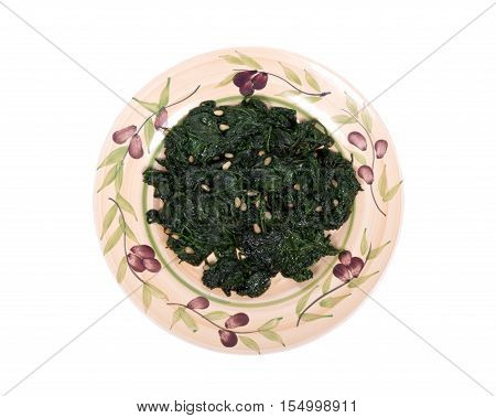 Sauteed fresh organic baby spinach with raw pine nuts on ceramic plate isolated on white background