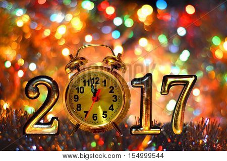 Figures 2017 and clock (new year ,Christmas) on bright background of holiday lights.
