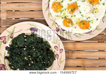 Fried eggs and sauteed spinach on ceramic plate and natural bamboo table