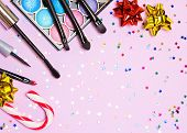 Makeup for festive party. Red lipstick, liquid eyeliner, mascara, bright color glitter eyeshadow, brushes and applicator with candy cane, gift wrap bow and confetti on pink background. Copy space poster