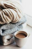 Stack of cozy knitted sweaters and thick yarn on window sill. Morning coffee in lazy winter weekend. poster