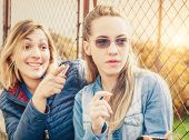 Two good mood girlfriends laughing and finger pointing poster