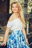 beautiful young woman in floral maxi skirt walking in spring poster