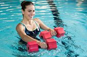 Fit woman working out with foam dumbbell in swimming pool. Woman engaged in doing aqua aerobics in water. Young beautiful woman doing aqua gym exercise with water dumbbell in swimming pool. poster