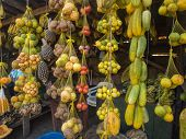 Tasty fresh colorful fruit hanging on a market stall in a small town. poster