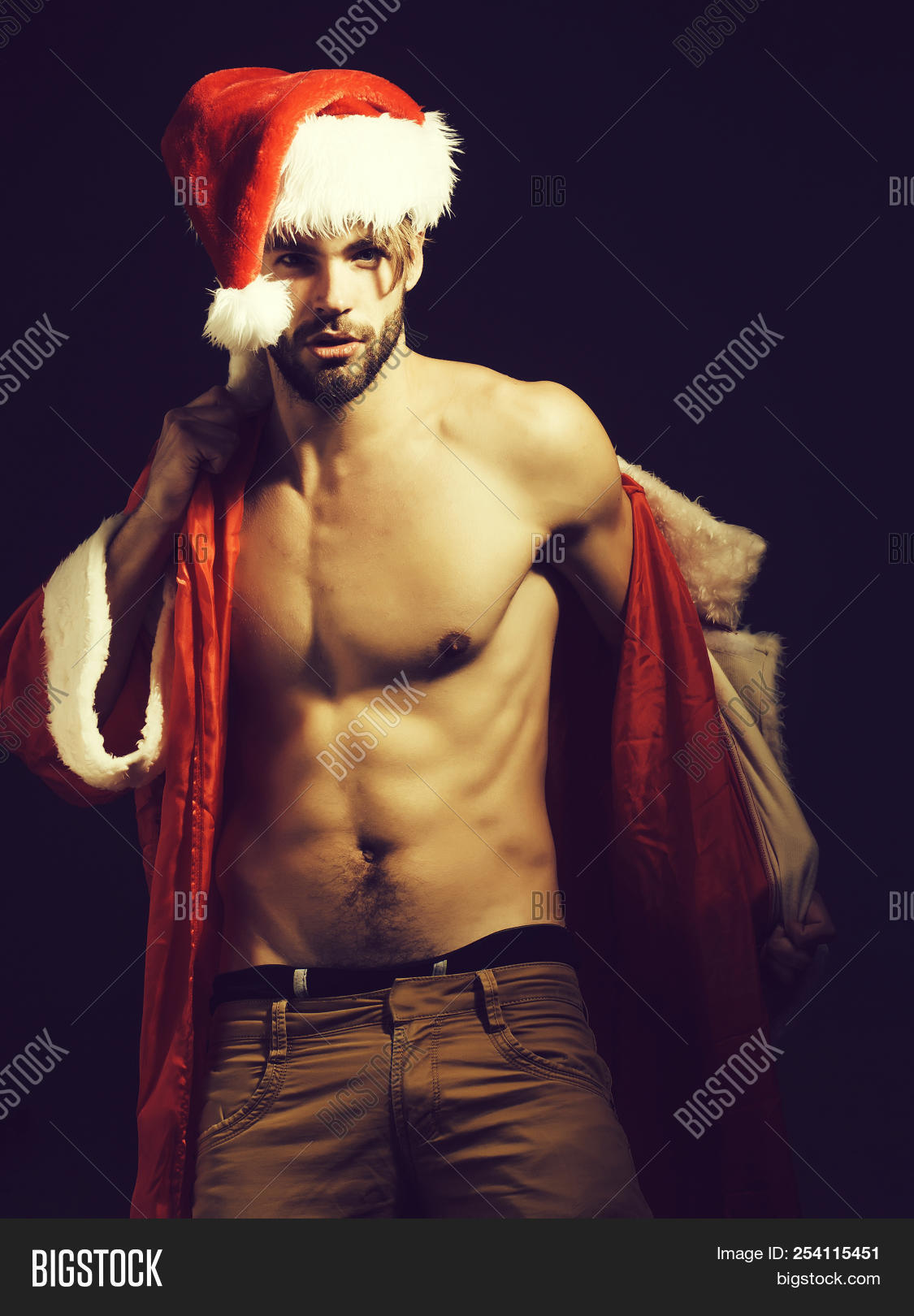 a4ce79cd984a1 Handsome santa claus guy sexy young bearded macho christmas man model in  red xmas or new year coat and hat has bare muscular torso and chest on  black ...
