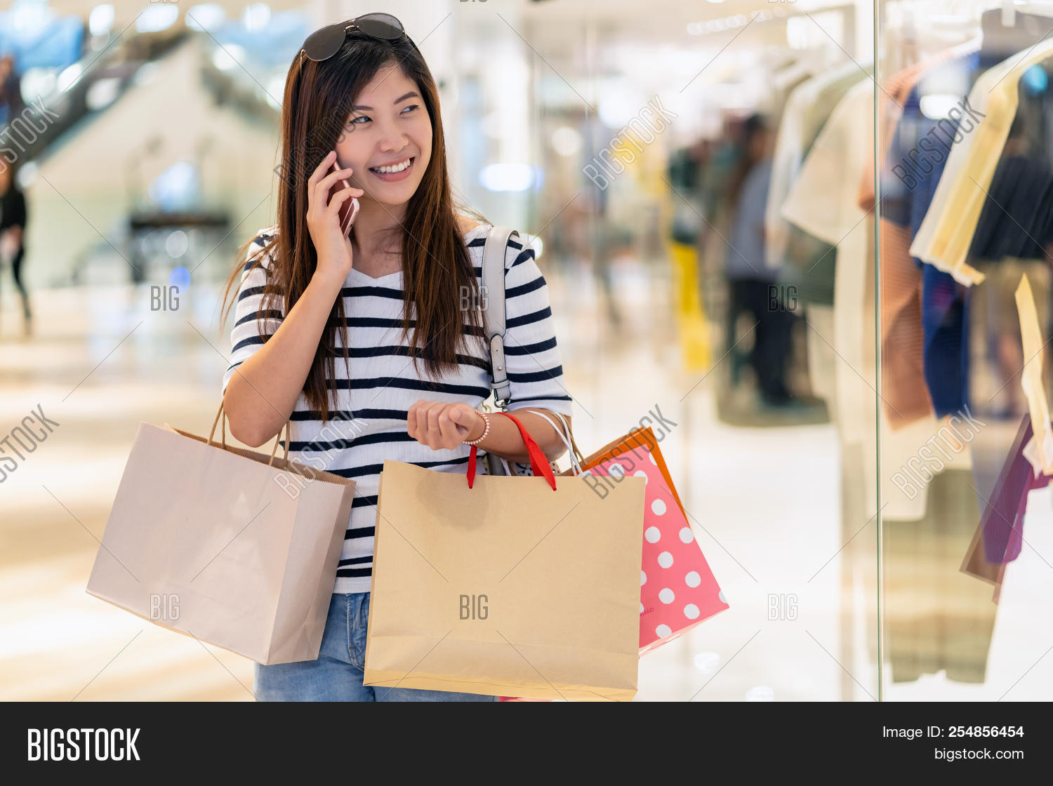 Happy Asian woman calling via the smart mobile phone for checking the  product and price and holding the shopping bag beside glass shop in  department store