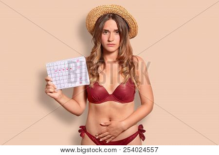 Displeased European woman feels pain during menstruation, keeps hand on bottom of belly, holds period calendar, wears summer hat and swimsuit, isolated over studio background. Female has periods poster