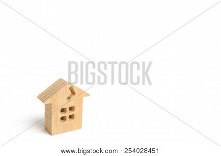 A Wooden House With A Crack. The Concept Of A Damaged House, Dilapidated Housing. Renovation, Repair