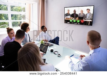 Group Of Skillful Businesspeople Video Conferencing In Boardroom