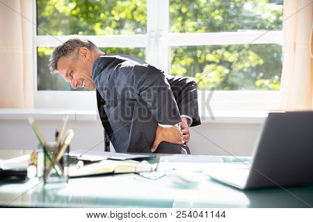 Side View Of A Mature Businessman Suffering From Back Pain In Office