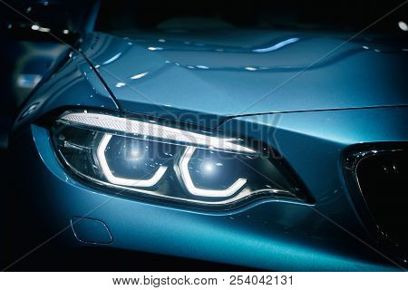 Car Headlight And Hood Of Powerful Sports Blue Car With Blue Glare On Dark Background. Close Up At C