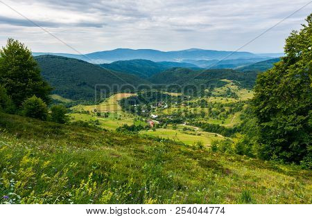 Beautiful Countryside Landscape In Mountains. Forested Hills And Village Down In The Valley. Overcas
