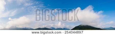 Wonderful Dynamic Cloudscape Above The Mountain Ridge. Beautiful Panoramic Nature Background