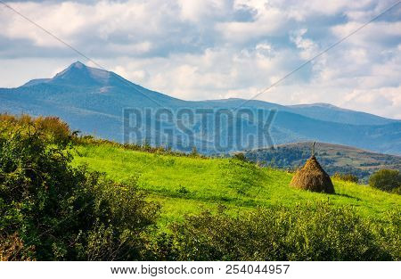 Haystack On A Grassy Slope. Ridge With High Peak In The Distance. Beautiful Agriculture Scenery In M