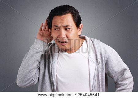 Young Asian Men Wearing Jacket Listen Whispers With Funny Face. Curious. Intently Listen In On Juicy