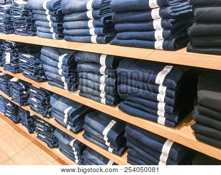 Jeans pants on the store shelf. Blue jeans denim Collection jeans stacked. Jeans Showcase, sale, shopping