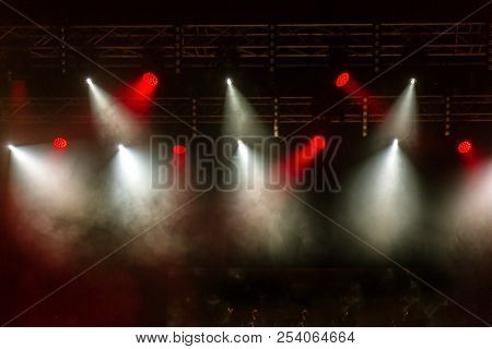 Stage Lights. Several Projectors In Dark. A Bright Colored Spotlight Permeates The Darkness. Light F