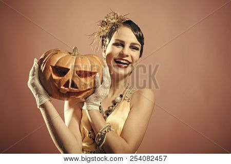 Halloween, Beauty And Vintage Fashion. Girl In Yellow Dress With Pumpkin. Halloween Holiday And Part