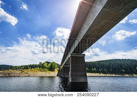 Concrete Bridge Over A River In Beautiful Nature Seen From Down Below