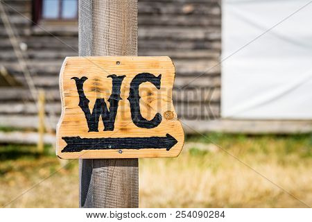 Wooden Wc Sign Showing The Direction To The Nearest Toilet In A Park