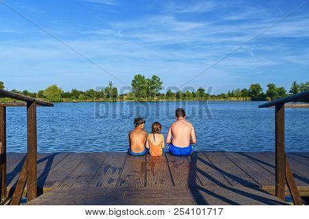 Children Sitting On Pier. Three Children Of Different Age - Teenager Boy, Elementary Age Boy And Pre