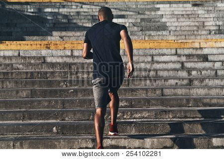 Achieving Best Results. Rear View Of Young African Man In Sports Clothing Running Up The Stairs Whil