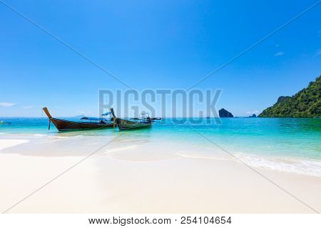 Longtail Boats Moored At Aonang Beach Against Blue Sky