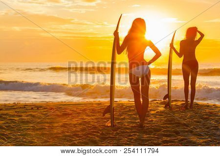Saturated, stylised, rear view silhouette of two beautiful sexy young women surfer girls in bikini with surfboards on a beach at sunset or sunrise