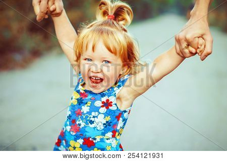 Parents Walk With Child Holding Hands Child Laughs