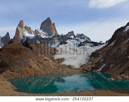 Sunny Mountains With Turquoise Lake. Snow Lying On The Slope Of The Mountain. Mountain Reflected In