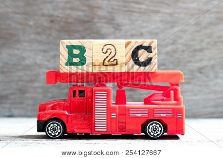 Toy fire ladder truck hold letter block in word b2c (Abbreviation of business to consumer) on wood background poster