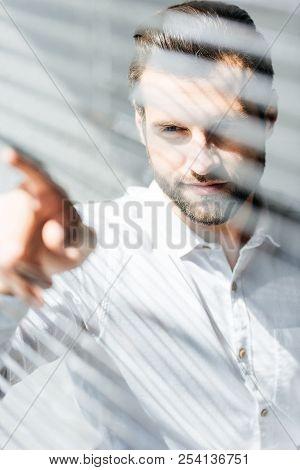 Handsome Man Looking Through Window Jalousie, Selective Focus