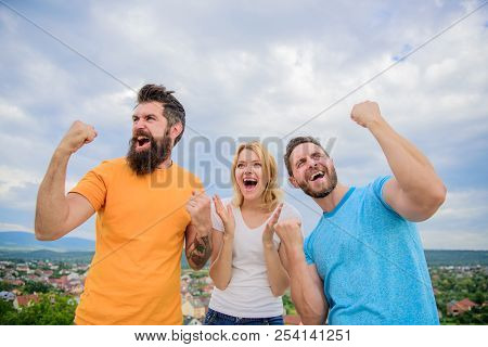 Woman And Men Look Emotional Successful Celebrate Victory Sky Background. Threesome Winners Happy Wi