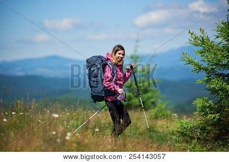Young Active Female Climber With Backpack And Trekking Sticks, Wearing Sports Wear, Trekking In The