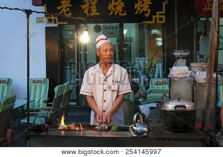 Dunhuang, China - August 7, 2012: Street Scene In The City Of Dunhuang, With A Cook Preparing Lamb K