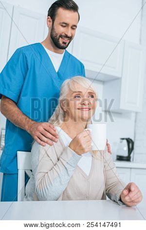 Smiling Male Caregiver Looking At Senior Woman Drinking Tea In Kitchen